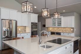 glass pendant lights quartz countertops white shaker cabinets and wood flooring in gilbert
