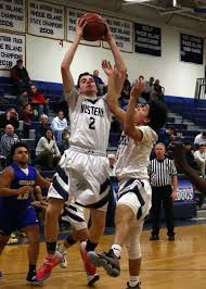 Westerly's Connor Warner (2) grabs a rebound with teammate Byron Dunn (3)  while Noah Warren (12) looks on for North Providence. The Westerly Bulldogs  boys varsity basketball team hosted the North Providence