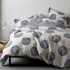 artistic duvet cover and sham with sundial motif on a textural stone colored ground