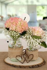reception centerpieces featured burlap-covered mason jars filled with  hydrangeas and baby's breath