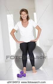 senior woman sitting on gym ball