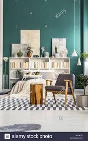 Grau Sessel Neben Einem Hölzernen Schemel Auf Gemusterten Teppich In
