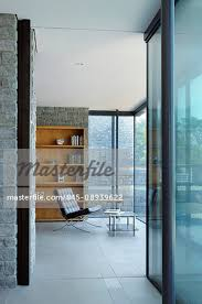 the interior spaces of a modern house on the cliffs overlooking the sea large glass panels and walls and wooden shelves and room dividers stock photo