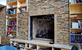 close up of a stone fireplace wall with built in wood bookshelves in an architect