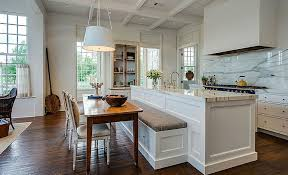 beautiful white kitchen with marble counters and backsplash with island and long bench seat