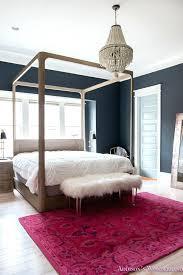 4 poster wood bed master bedroom black walls white wood bead chandelier whitewashed hardwood flooring four
