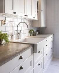 concrete countertop a sink white cabinets subway tile backsplash