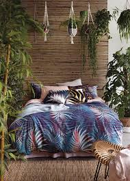 a tropical theme bedroom due to the bedding and throw pillow covers the plants add