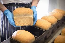 Baker Holding Loaf Of Freshly Baked Bread Stock Photo Dissolve