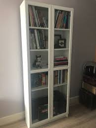 white bookcase shelving unit with glass doors