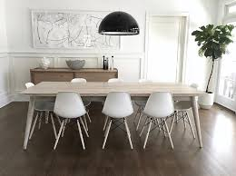 light gray stained dining table with white eames molded plastic chairs