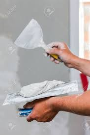 handyman smoothing drywall before painting when renovation the house stock photo 70770547