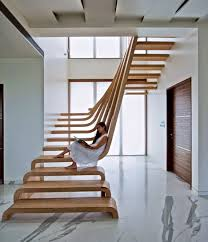 a u shaped staircase made from walnut with open treads allowing natural light to fill the interior space allowing natural light fill
