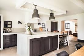 white kitchen with dark wood island that has white surface that waterfalls down the ends