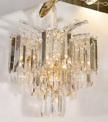 a vintage brass frame chandelier with suspended lucite prisms and a waterfall spray style top