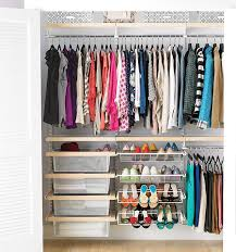the container s elfa closet system installed in a closet full of colorful clothes and