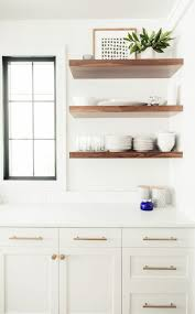 all white kitchen with wood accents love these floating shelves floating pantry