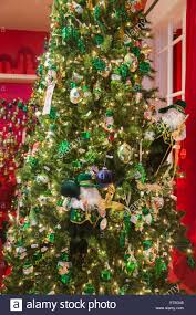 Festive green and gold Christmas decorations with an Irish theme on a Xmas  tree in a store in New York, USA