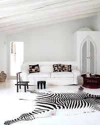 dalmatian print rug a large zebra print rug and dark stools accentuate a white living room