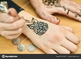 одаренный девушка рисует узоры хной на руках стоковое фото