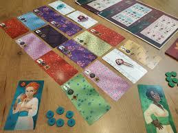 En primer lugar, debemos desplegar la propia caja del juego de mesa (idea original y cómoda) que se convierte en nuestra tablero de puntuación que, siguiendo la temática japonesa, hace alusión a los kakemonos del arte japonés (soporte de las obras artísticas).a su vez, cada jugador elige la dama y el color de sus botones para confeccionar su kimono. Kimono El Juego De Mesa Del Arte Japones