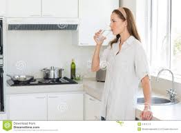 Home Drinking Water Side View Of A Woman Drinking Water In Kitchen Stock Photos