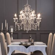 twelve light dual mount chrome chandelier hangs in dining room long back chairs also chic white plate and candle holder