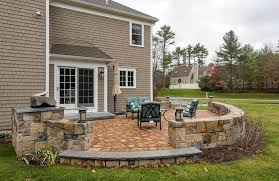 backyard raised stone patio with small wall and outdoor lighting