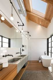 A skylight illuminates the neutral master bathroom, letting bathers  contemplate the clouds. The faucets