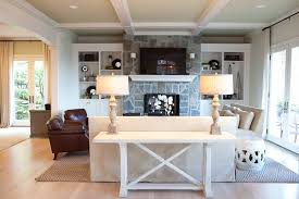 sofa table with unique table lamps and brown leather armchair also fireplace mantel and coffered ceiling with built in shelves plus french doors for living