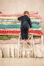 princess and the pea bed. Child Climbs On The Bed With Lots Of Quilts - Princess And Pea. Stock Pea