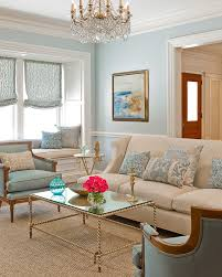Pretty blue walls and gold coffee table. Cream, blue and seascape living  room.
