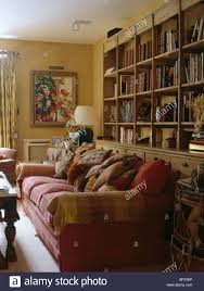 Living Room With Red Sofa Red Sofa Piled With Cushions In Front Of Large Fitted Bookcase In