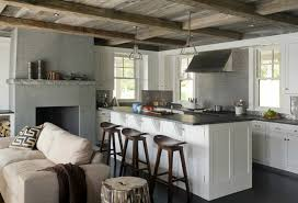 Rustic kitchen with floor to ceiling white cabinets paired with soapstone  countertops and stainless steel kitchen tile kitchen backsplash.