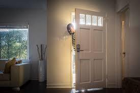 open front door. Father Arriving Home Peeping Through Open Front Door Stock Photo