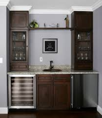 wet bar in home with fridge sink and cabinets