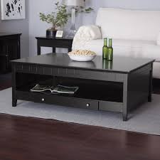 rectangle black wooden coffee table with shelf and single drawer on the bottom side placed on