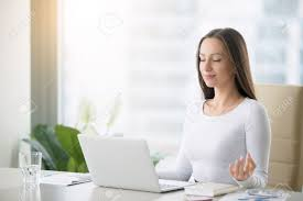 meditation office. Stock Photo - Young Woman Near The Laptop, Practicing Meditation At Office Desk, In Front Of Online Yoga Classes, Taking A Break Time For R