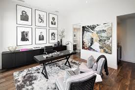 a collection of black and white framed photographs and wall add to the neutral color scheme