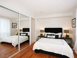 minimalist furniture layout idea for small bedroom with mirrored wardrobe with sliding doors and queen size