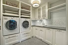 Stunning White Laundry Room Cabinets Ideas at Transitional Laundry Room  with Small Tile Backsplash and Concrete
