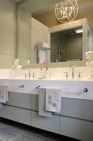 gray bathroom vanity with clear glass towel bars