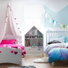 children s bedroom with two single beds fabric canopy and blue chevron painted wall