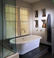 tasteful glass divider corner shower room with oval freestanding tubs in white also built in caddy