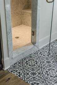 black and white terranean bathroom features a white gray and black mosaic tiled floor placed