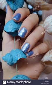 Blue Glitter Nail Designs Female Hands With Blue Glitter Nail Design Holding Sea Shell