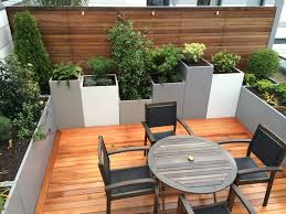 Exterior:Small Kings Cross Roof Rerrace With Round Wooden Table And  Container Garden Also Wooden