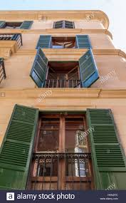 Majorcan Spanish style with windows and green shutter doors with ...