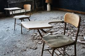 empty chairs empty tables chunks of fallen plaster lie among traditional school desks marked
