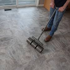 using a 100 pound roller to bond tile flooring